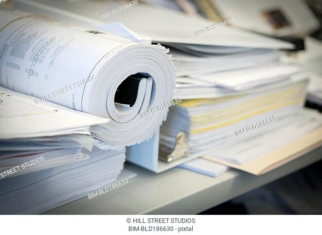 Close up of rolled blueprints in stack of paper