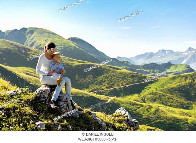 Germany, Bavaria, Oberstdorf, mother and little daughter on a hike in the mountains having a break