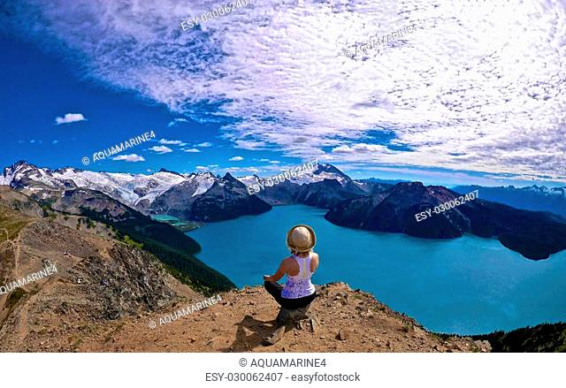 Woman sitting on the cliff above glorios Garibaldi lake surrounded with snowcapped mountains. Garibaldi Provincial Park, British Columbia, Canada