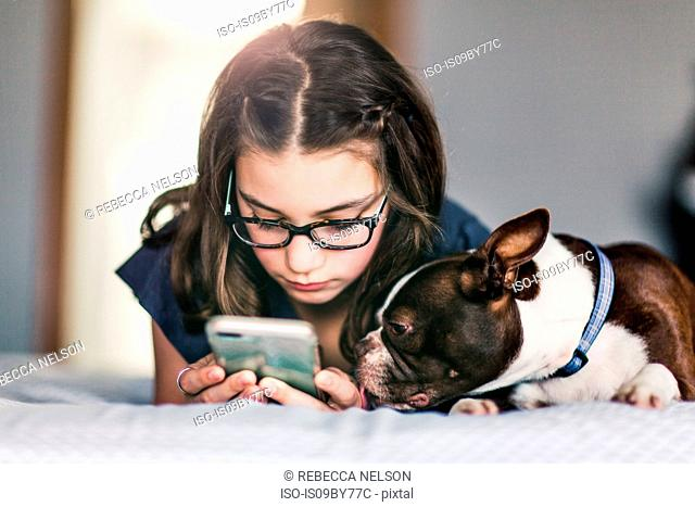 Girl using smartphone beside pet dog on bed
