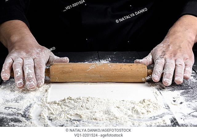 wooden rolling pin in male hands, next is scattered white wheat flour