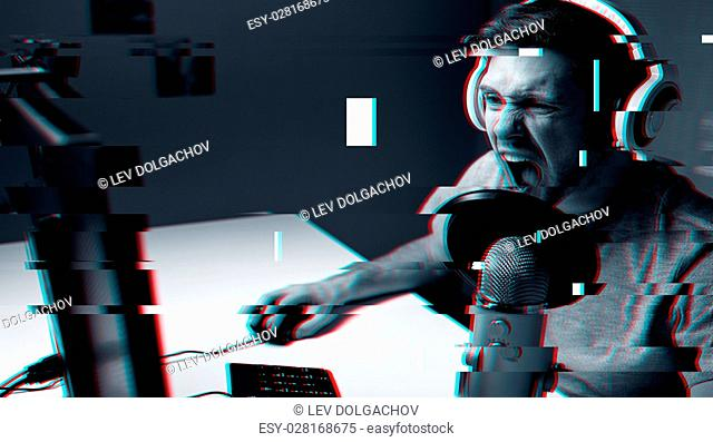 technology, gaming, entertainment and people concept - angry screaming young man in headset with pc computer playing game at home and streaming playthrough or...