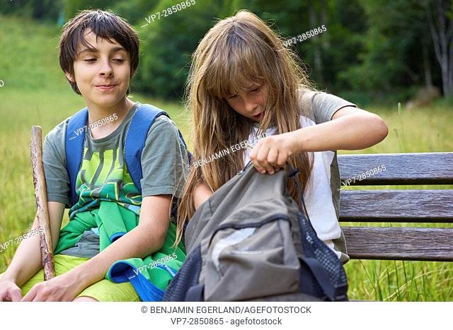 young boy is smiling about a girl who is searching in her backpack