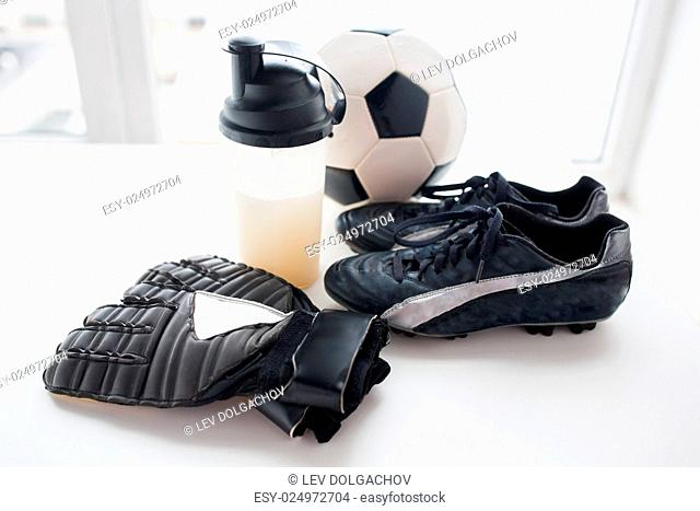 sport, football and sports equipment concept - close up of soccer ball, boots, goalkeeper gloves and protein shake bottle with drink