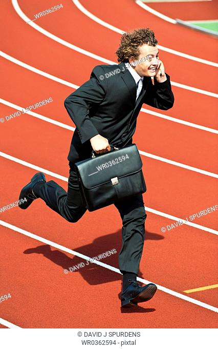 Businessman on cell phone with briefcase running fast on athletics track