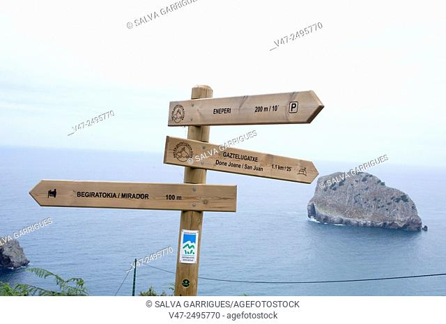 Tourist signs for walkers and Gaztelugatze the background Aquech Island, Bermeo, Biscay, Basque Country, Spain, Europe