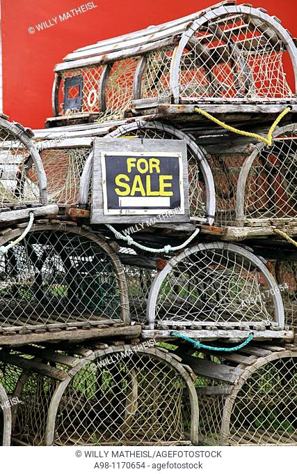 stacked traditional wooden lobster traps and sale sign in front of a red building, Nova Scotia, Canada