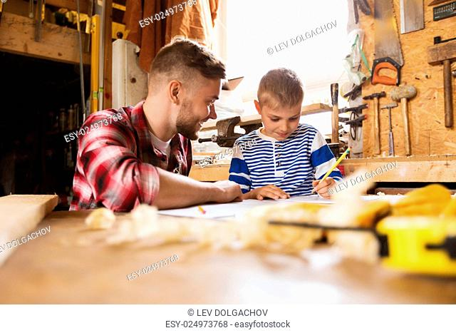family, carpentry, woodwork and people concept - happy father and little son with blueprint at workshop