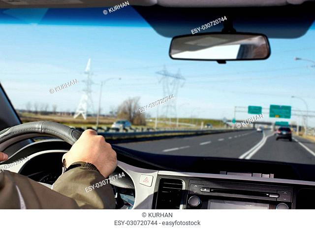 Hand of man driving on a highway. Driver insurance concept
