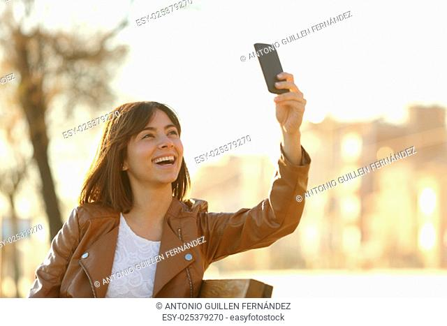 Woman taking selfie photo with a smarphone in winter sitting in a bench in a park