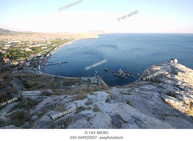 Luxurious view of the bay from the rocky cliffs to the sea with beaches and hotels on the shore with a dock and boats standing next to it