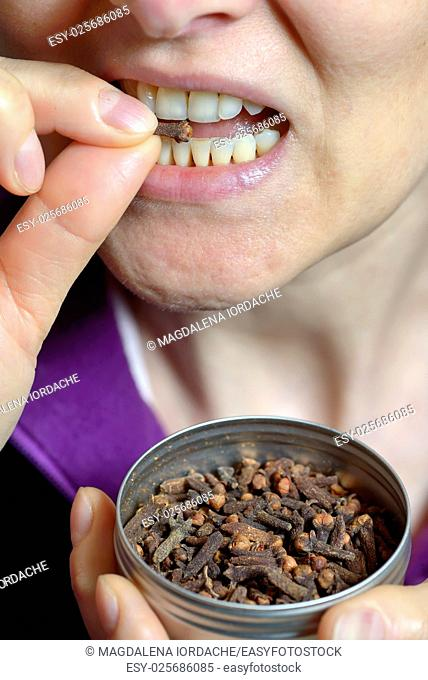Woman chew dried clove spice for fresh breath