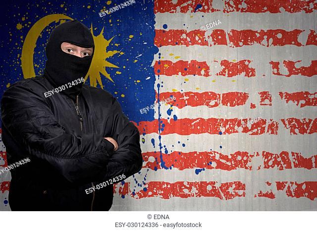 dangerous man in a mask standing near a wall with painted national flag of malaysia