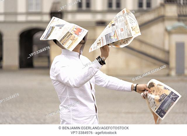 Man assailed by flying newspapers, in Munich, Germany