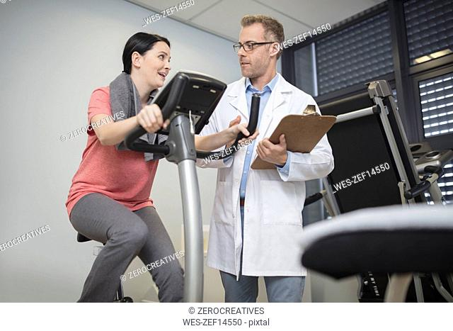 Doctor talking to patient on exercise machine