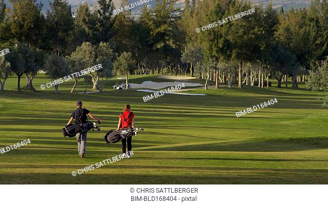Caucasian couple carrying golf bags on course