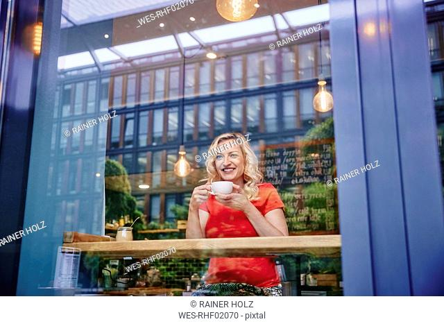 Smiling blond woman drinking coffee in a cafe