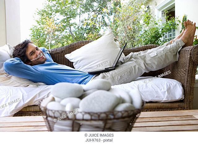 Man lying on sofa with laptop on lap, smiling, portrait, bowl of pebbles in foreground differential focus