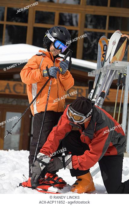 A father helps his son with his skis and bindings, Whistler Mountain, British Columbia, Canada
