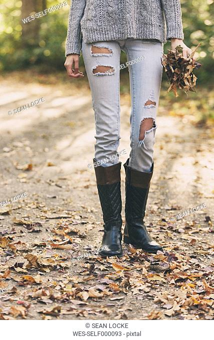 Teenage girl standing on path holding autumn leaves