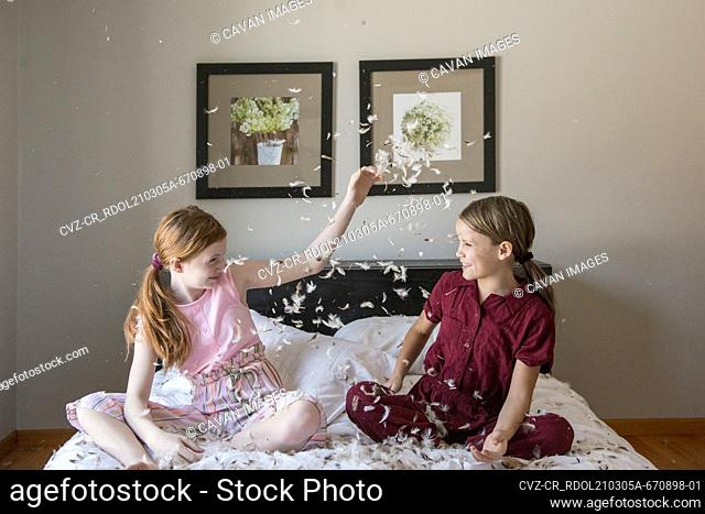 Two happy young girls having a feather pillow fight on the bed