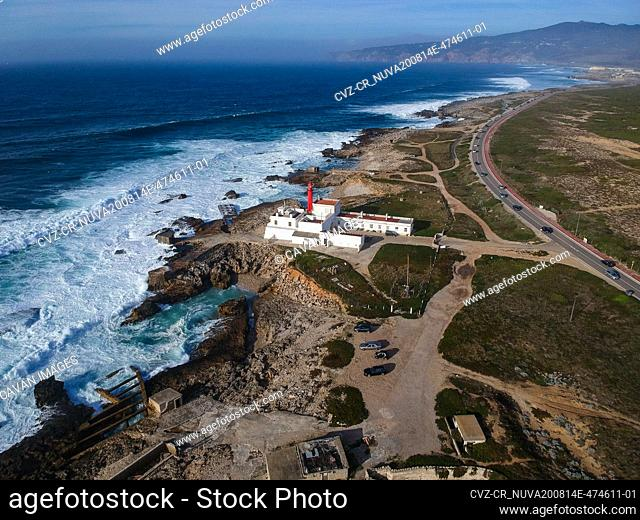 Aerial view of rocky coastline with a Lighthouse and a road