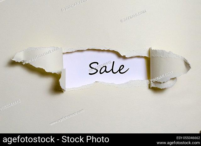 The word sale appearing behind torn paper