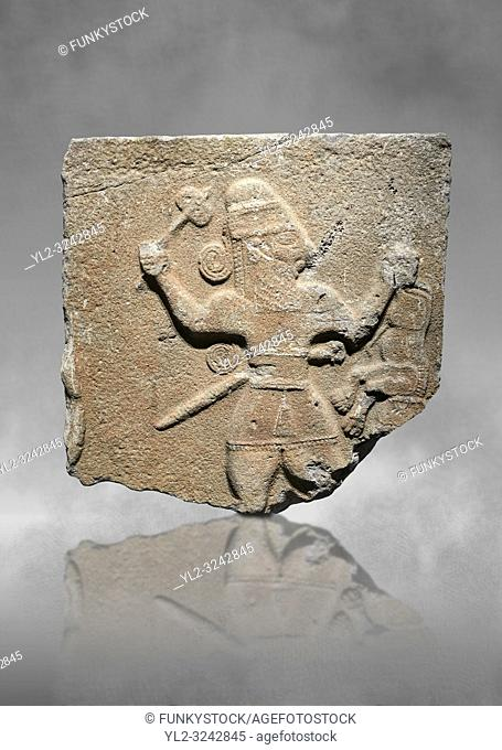 Hittite monumental relief sculpture of a man with an axe in one hand about to use it to kill a lion he is holding updide down in his other hand