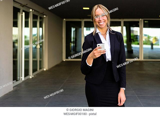Portrait of laughing businesswoman with cell phone
