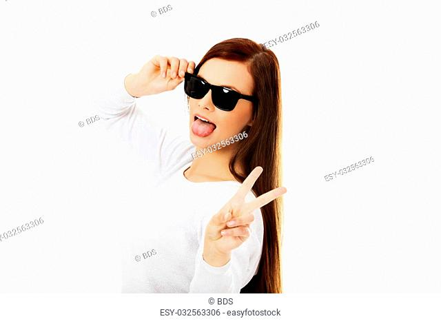 Happy brunette woman in sunglasses shows tongue and victory sign
