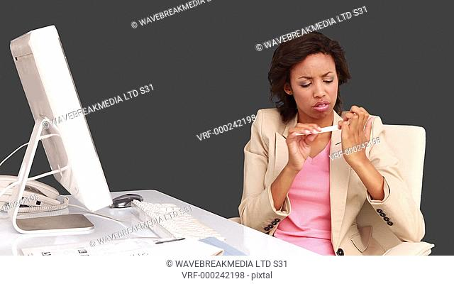 Businesswoman filing her nails at her desk on grey screen background