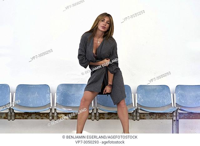 attractive woman without trousers, posing with sexy attitude, in front of row of blue chairs. Russian ethnicity. In holiday destination Hersonissos, Crete