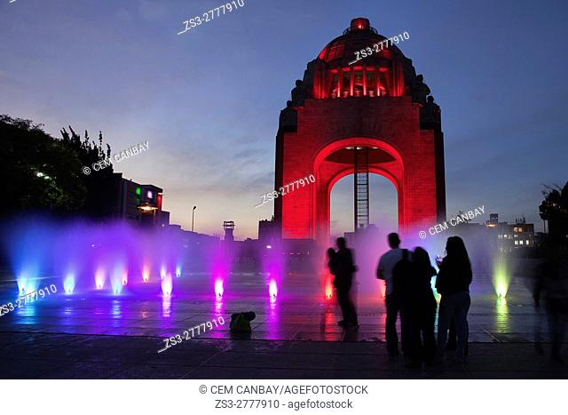 People in front of the Monument dedicated to the Mexican Revolution (Monumento dedicado a la Revolucion Mexicana) with colorful water show and silhouettes of...