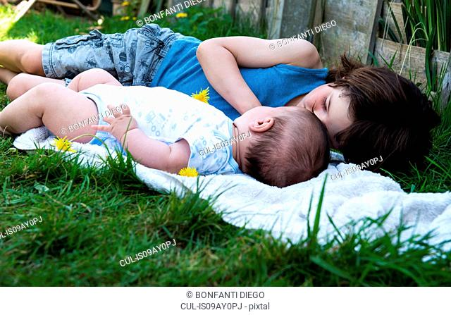 Boy and baby brother gazing at each other in garden