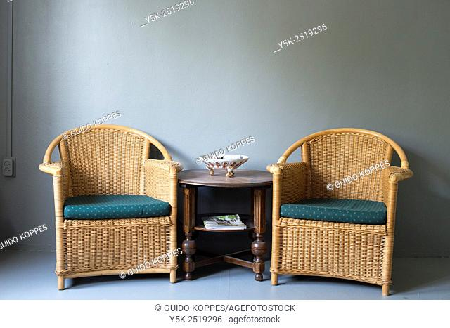 Tilburg, Netherlands. Rattan chairs and antique wooden table, forming a small seating inside a photographers studio