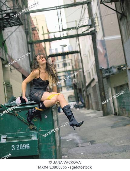 Woman sitting on a trash bin in an alley way