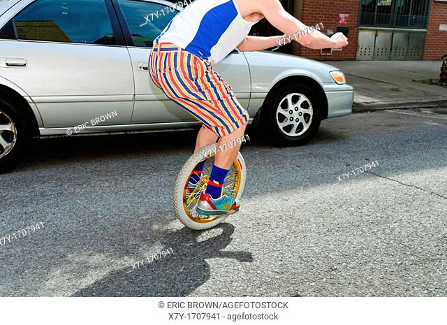 A man rides an Impossible Wheel or BC wheel  It is basically a unicycle without pedals, a seat post, or a seat