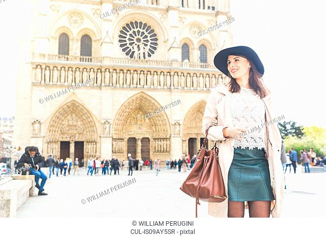 Stylish young woman strolling in front of Notre Dame, Paris, France