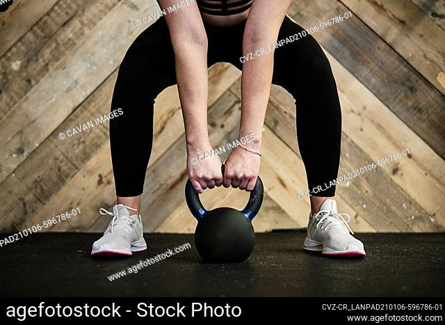 close-up of fit woman in exercise gear lifting a kettlebell at the gym