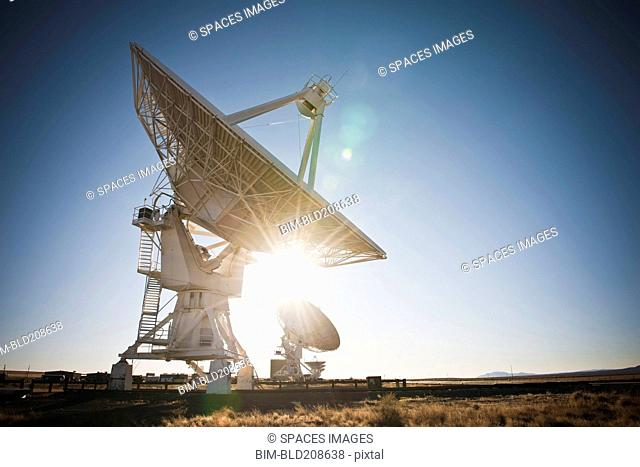 Sun shining behind satellite dish in desert, Socorro, New Mexico, United States