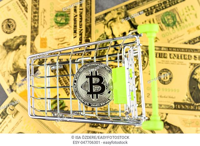 View of metal bitcoin in shopping trolley over American dollar banknotes . Concept image for cryptocurrency