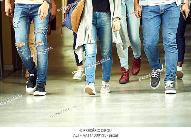 Students walking in school corridor, low section