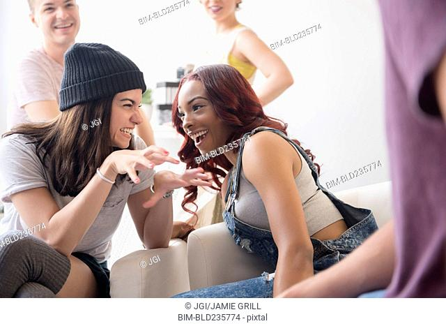 Friends gesturing and laughing at party