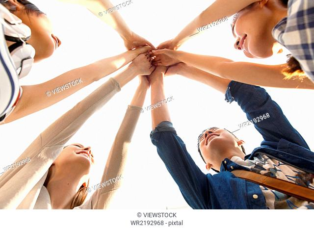 Young people in circle with hands together