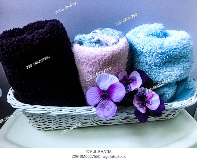 A functional and decorative arrangement of towels and flowers in a wicker basket, often seen in contemporary Western style bathrooms with an oriental touch