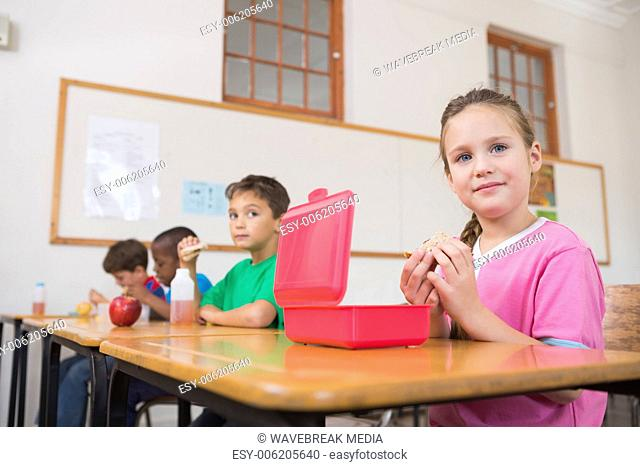Cute pupils having their lunch in classroom