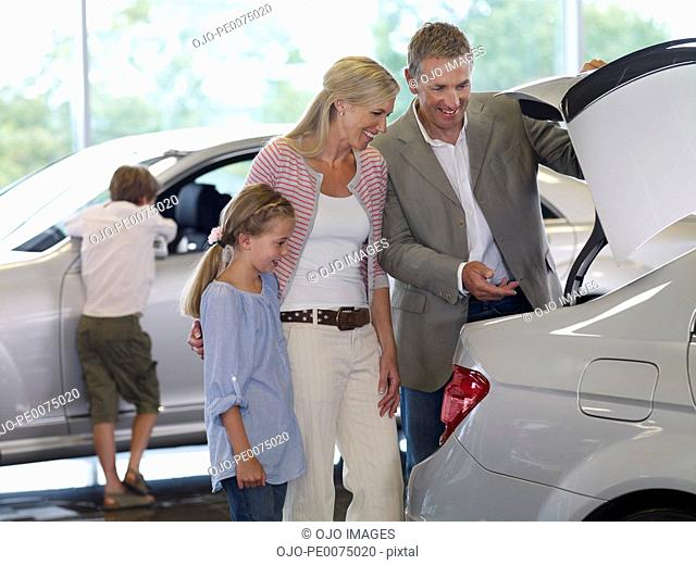 Family looking new car in showroom
