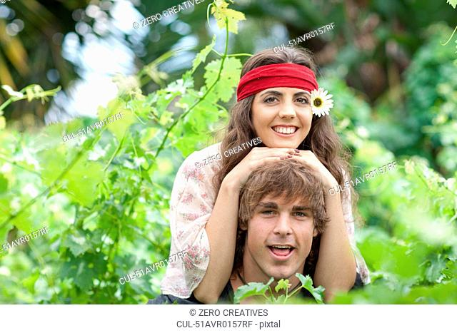 Man carrying girlfriend in tall plants