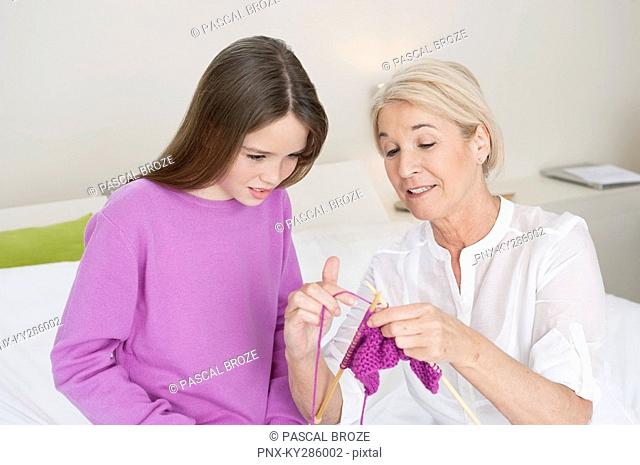 Woman teaching her granddaughter to knit