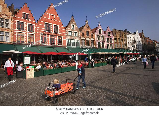 Woman with a baby carriage in front of the colorful traditional buildings used as restaurants on the Market Square, Bruges, West Flanders, Belgium, Europe